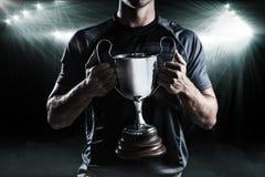 Samengesteld beeld 3D van zegevierende de holdingstrofee van de rugbyspeler Royalty-vrije Stock Foto's