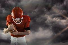 Samengesteld beeld die van Amerikaanse voetbalster voetbal beschermen Stock Afbeeldingen