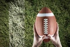 Samengesteld beeld die van Amerikaanse voetbalster voetbal steunen Stock Foto's