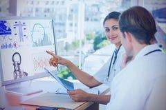 Samengesteld beeld die van arts het scherm van een computer tonen aan een collega royalty-vrije illustratie