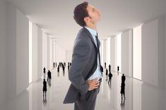 Samengesteld beeld die van ernstige zakenman zich met handen op heupen bevinden Stock Afbeeldingen