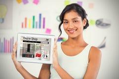 Samengesteld beeld die van gelukkige onderneemster digitale tablet in creatief bureau tonen royalty-vrije stock fotografie