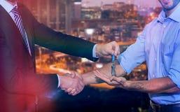 Samengesteld beeld die van glimlachende zakenman sleutels geven en handen schudden royalty-vrije stock afbeelding