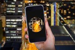 Samengesteld beeld die van hand mobiele telefoon houden tegen witte achtergrond Stock Foto