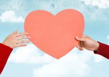 Samengesteld beeld die van handen een roze hart houden Royalty-vrije Stock Afbeelding