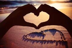 Samengesteld beeld die van handen hartvorm op het strand maken stock foto