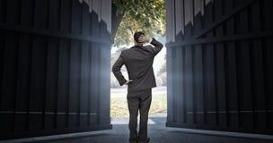 Samengesteld beeld die van jonge zakenman zich terug naar camera bevinden die zijn 3d hoofd krassen Royalty-vrije Stock Foto's