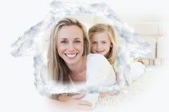 Samengesteld beeld die van moeder en dochter op de vloer liggen Stock Afbeeldingen