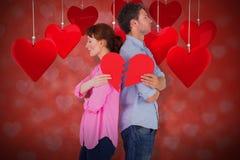 Samengesteld beeld die van paar een gebroken hart 3D houden Royalty-vrije Stock Afbeeldingen