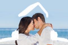 Samengesteld beeld die van paar en elkaar op het strand omhelzen kussen Royalty-vrije Stock Foto's