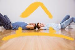 Samengesteld beeld die van paar op de vloer liggen Stock Foto's