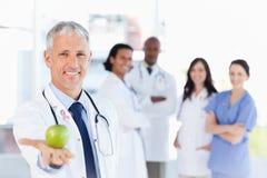 Samengesteld beeld die van rijpe arts een appel houden Stock Foto's