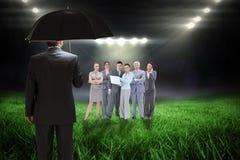 Samengesteld beeld die van rijpe zakenman een paraplu houden Stock Afbeeldingen