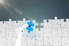 Samengesteld beeld die van robotachtig wapen blauw figuurzaagstuk houden door 3d raadsel Stock Afbeeldingen