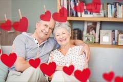 Samengesteld beeld die van rood hart en hoger paar op bank omhelzen Royalty-vrije Stock Foto