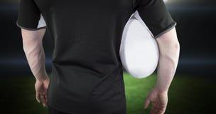 Samengesteld beeld die van rugbyspeler een rugbybal houden Royalty-vrije Stock Afbeeldingen