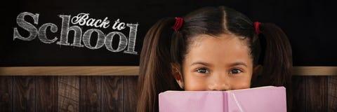 Samengesteld beeld die van schoolmeisje mond behandelen met boek stock fotografie