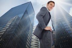 Samengesteld beeld die van vrolijke zakenman zich met handen op heupen bevinden royalty-vrije stock afbeeldingen