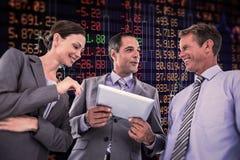 Samengesteld beeld die van zakenman tablet tonen aan zijn collega's Royalty-vrije Stock Foto