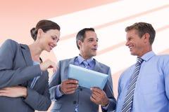 Samengesteld beeld die van zakenman tablet tonen aan zijn collega's Stock Fotografie