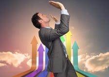 Samengesteld beeld die van zakenman zich met wapens bevinden die omhoog drukken Stock Afbeelding