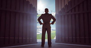 Samengesteld beeld die van zakenman zich terug naar de camera met handen op 3d heup bevinden Stock Foto's