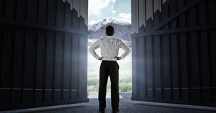 Samengesteld beeld die van zakenman zich terug naar de camera met handen op 3d heupen bevinden Royalty-vrije Stock Fotografie