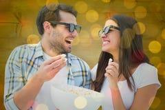 Samengesteld beeld van aantrekkelijk jong paar die op een 3d film letten Royalty-vrije Stock Afbeelding