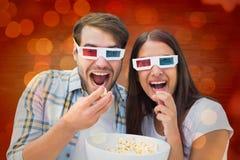 Samengesteld beeld van aantrekkelijk jong paar die op een 3d film letten Stock Afbeeldingen