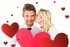 Samengesteld beeld van aantrekkelijk jong paar die rood hart houden Royalty-vrije Stock Foto