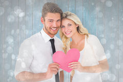 Samengesteld beeld van aantrekkelijk jong paar die roze hart houden Royalty-vrije Stock Afbeeldingen