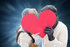 Samengesteld beeld van aantrekkelijk jong paar die in warme kleren rood hart houden Stock Afbeeldingen