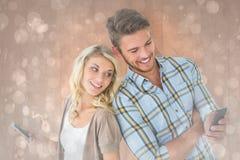 Samengesteld beeld van aantrekkelijk paar die hun smartphones gebruiken Royalty-vrije Stock Afbeelding