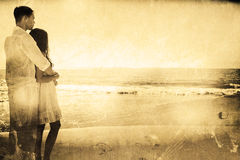 Samengesteld beeld van aantrekkelijk paar die uit op zee kijken royalty-vrije stock afbeeldingen