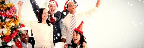Samengesteld beeld van aardig commercieel teamponsen de lucht om Kerstmis te vieren stock foto