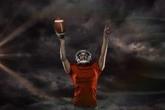 Samengesteld beeld van Amerikaanse voetbalster met de wapens opgeheven van de holdingsbal Stock Foto's