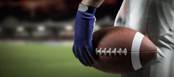 Samengesteld beeld van bebouwd beeld die van sportman de Amerikaanse bal van de voetbalbal houden Royalty-vrije Stock Foto