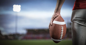 Samengesteld beeld van bebouwd beeld van de Amerikaanse bal van de voetbalsterholding Stock Foto