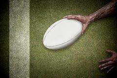 Samengesteld beeld van bebouwd beeld van een het rugbybal van de mensenholding Royalty-vrije Stock Afbeelding
