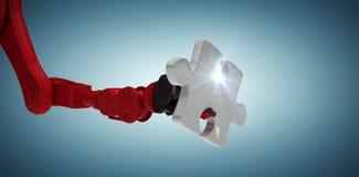 Samengesteld beeld van bebouwd beeld van rode robotachtige hand met 3d raadselstuk Stock Afbeeldingen