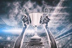 Samengesteld beeld van bebouwde hand van 3D de trofee van de atletenholding Stock Fotografie