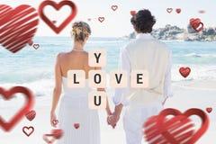 Samengesteld beeld van bruid en bruidegomholdingshanden die uit aan overzees kijken Royalty-vrije Stock Foto