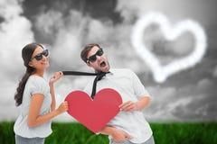 Samengesteld beeld van brunette die haar vriend trekken door het hart van de bandholding Stock Foto
