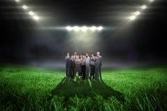 Samengesteld beeld van commercieel team die camera bekijken Stock Afbeelding