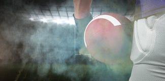 Samengesteld beeld van de Amerikaanse bal van de voetbalsterholding Royalty-vrije Stock Afbeeldingen