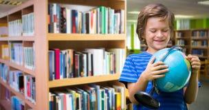 Samengesteld beeld van de gelukkige bol van de jongensholding terwijl status Royalty-vrije Stock Afbeeldingen