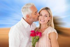 Samengesteld beeld van de hartelijke mens die zijn vrouw op de wang met rozen kussen Stock Afbeelding
