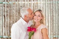Samengesteld beeld van de hartelijke mens die zijn vrouw op de wang met rozen kussen Stock Foto