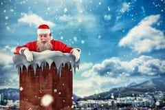 Samengesteld beeld van de Kerstman die over muur gluren Stock Foto