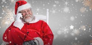 Samengesteld beeld van de Kerstman die telefoon op stoel met behulp van royalty-vrije stock foto